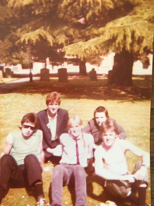 Two members of The Undertones (front right and front left) with Mary Simcox (centre) and two friends in the churchyard at Malvern Priory, 17 May 1980 | Mary Simcox